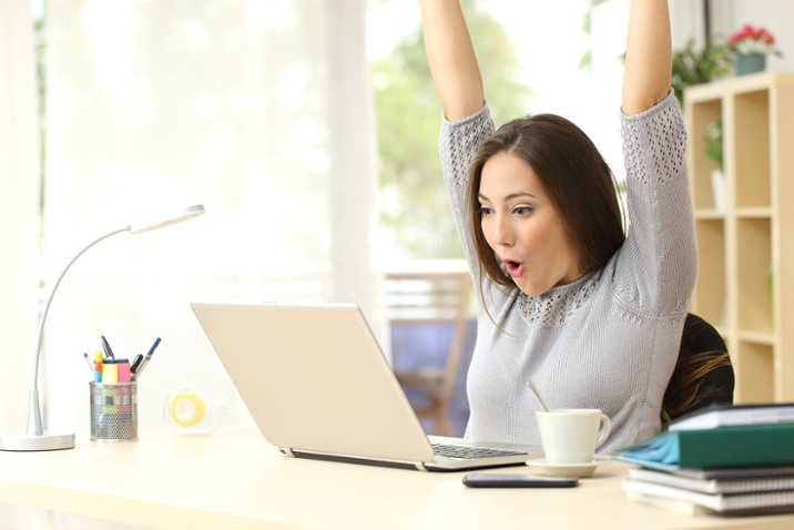 woman excited on computer for paying off her debt faster